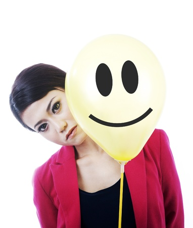 hypocritical: Unhappy businesswoman hides behind a smiley face isolated on white