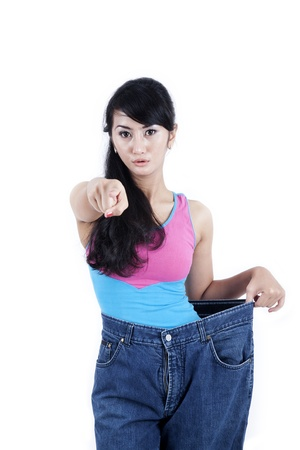 Beautiful Asian woman shows her old huge pair of jeans while pointing to people at front of her photo