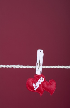 Valentine photo concept: two hearts hanging on a cloth line photo