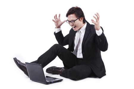 Angry businessman looking at his laptop isolated on white photo