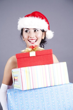 Asian woman wearing christmas hat holding christmas presents photo