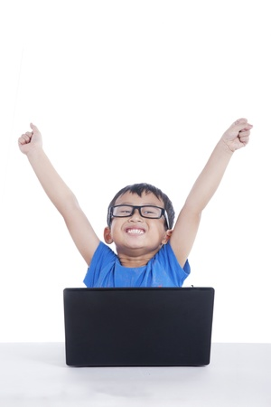 Happy Asian toddler with glasses using laptop computer isolated on white photo