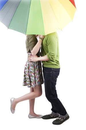 hugs and kisses: Cute couple kissing under the umbrella isolated on white Stock Photo
