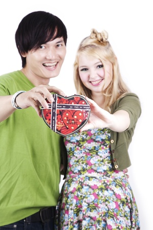 Cute asian-caucasian couple holding a heart shaped box isolated on white photo