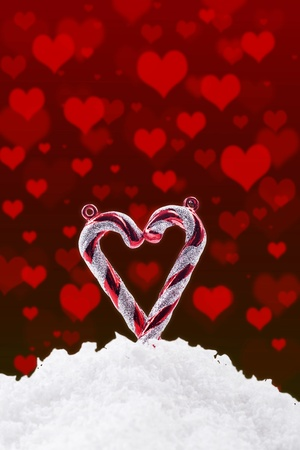 Heart made of candy cane with snow and hearts photo