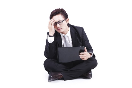 Businessman with headache sits on floor with this laptop isolated on white Stock Photo - 12150408