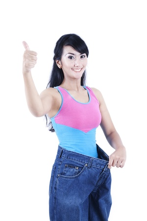 Weight loss concept: asian woman showing off her big old jeans Stock Photo - 11598141