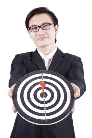 Asian businessman holding dartboard on white background photo