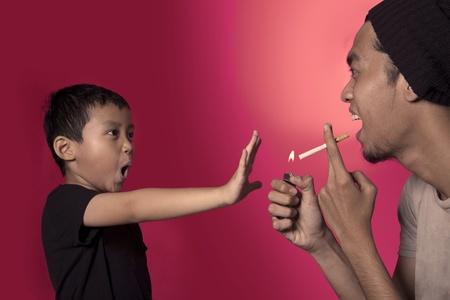 Cute asian boy asking a smoker to stop smoking photo