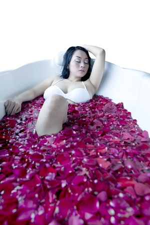 Asian woman enjoying the day having a  bath  with rose petals photo