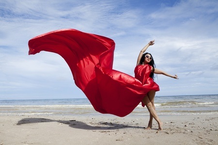 beach wrap: Beautiful woman with a red scarf on the beach Stock Photo