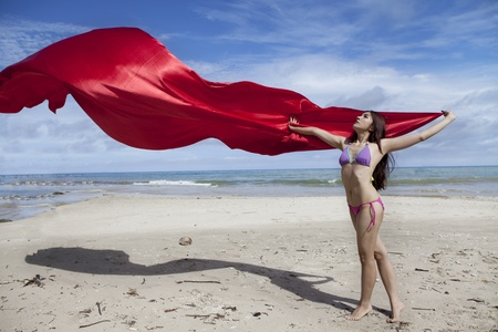 Asian woman with red scarf enjoying freedom on the beach photo