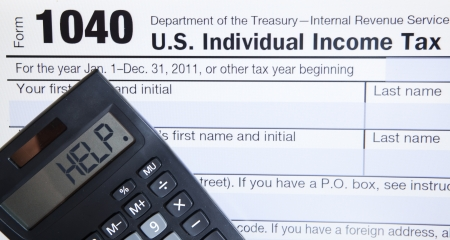 income tax: Electronic Tax form 1040 with the help word on calculator Stock Photo