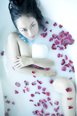 Sensual Asian woman having a bath with rose petals photo