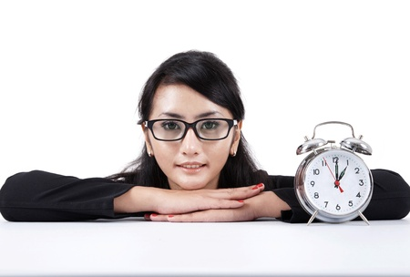 looking at watch: Smiling beautiful businesswoman with alarm clock