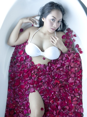 Beautiful asian woman bath flower with rose petals photo