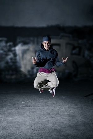 Performing dancer flying while posing breakdance outdoor photo