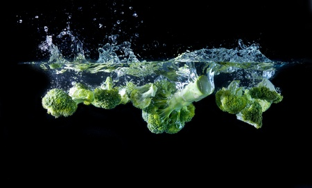 Green broccoli falling in water with bubbles and splashes photo