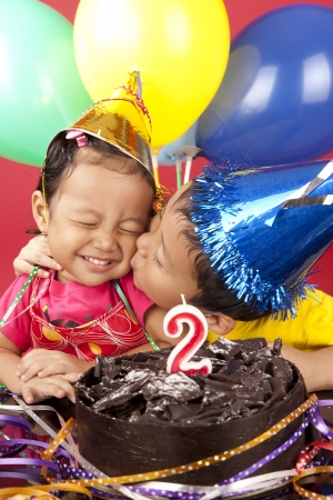 asian toddler: Asian brother kisses his sister on her birthday