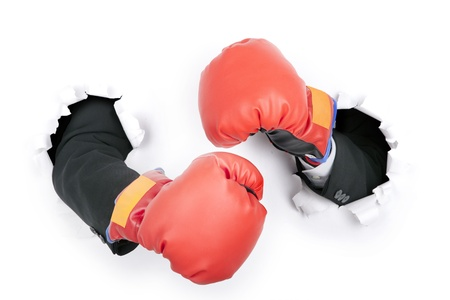 boxing training: Businessmans hand breaking through a paper wall wearing boxing gloves