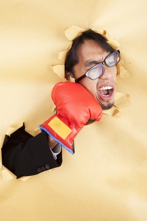 Businessman hitting himself with a red boxing glove in the face photo