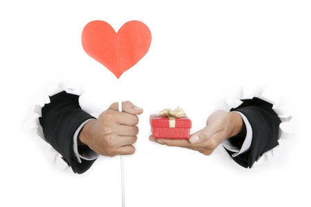 Isolated businessmans hand holding gift and heart shape on white photo