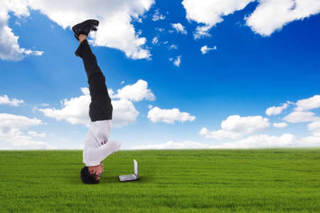 Atractive businessman headstand outdoors photo