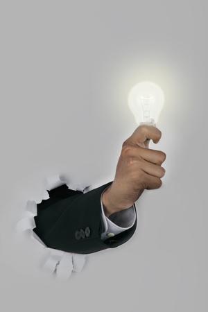 notion: Businessman hand breaking through a paper wall holding an illuminated light bulb