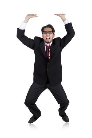 Joven hombre de negocios asiático llevando algo pesado por encima de su disparo en la cabeza en el estudio aislado en blanco Foto de archivo - 12150211