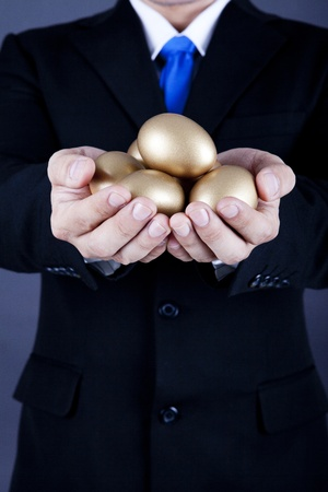 huevos de oro: Hombre de negocios la celebraci�n de los huevos de oro - un concepto de inversi�n