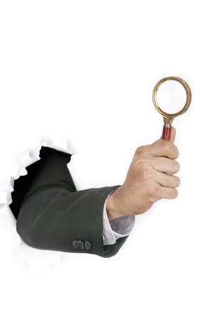 snoop: Businessman hand investigate breaking through a paper wall holding  a magnifying glass