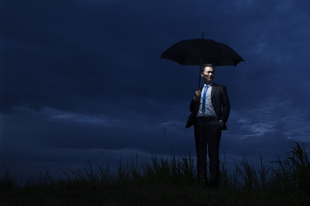 Asian businessman with umbrella standing on a cloudy day photo
