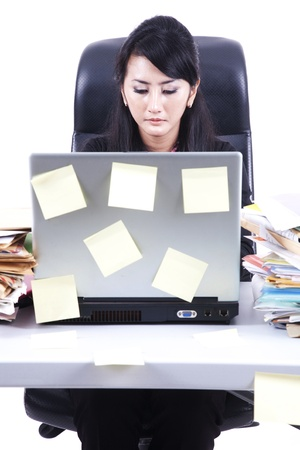 Businesswoman working on her desk with laptop and notepad photo