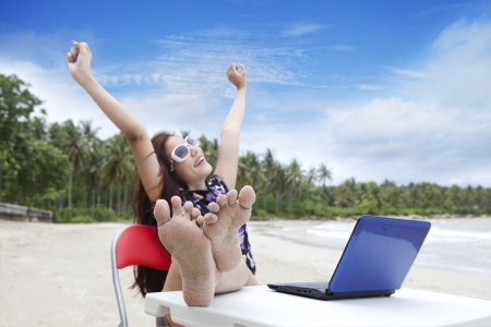 Happy businesswoman enjoying beautiful beach with laptop photo