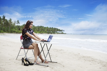Asian businesswoman working at beach photo