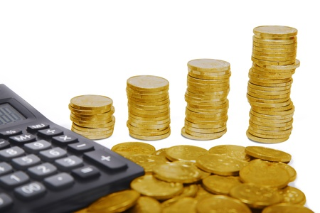 Calculator and stack of golden coins photo