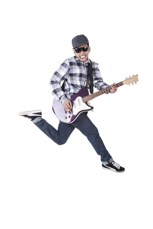 Asian guy with guitar jumping isolated on white photo