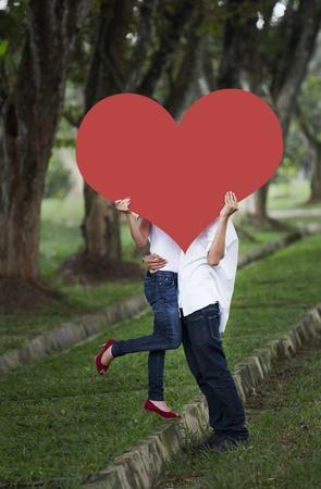pareja besandose: Joven pareja besándose detrás de recorte de corazón rojo en la naturaleza