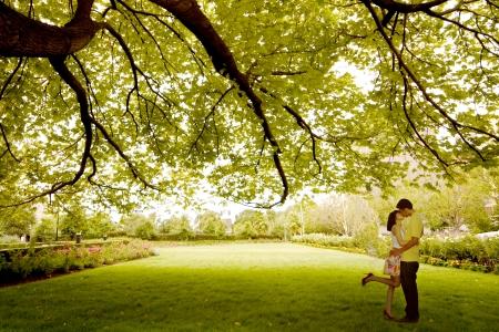 enamorados besandose: Joven pareja bes�ndose bajo el �rbol de Asia Foto de archivo