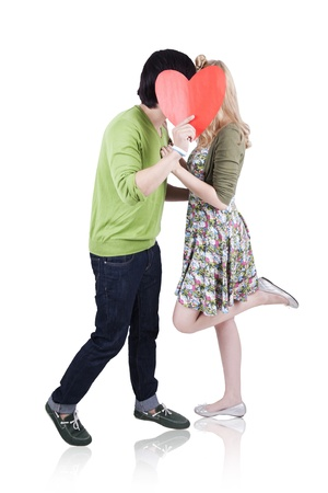 Caucasian couple kissing while hiding behind a cut out heart isolated on white photo