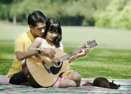 Romantic young couple playing guitar in the park photo