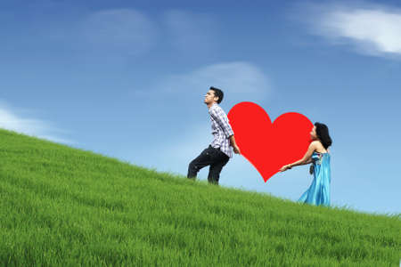 married couples: Asian couple walking up hill carrying a huge heart cutout
