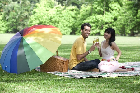 Asian young couple with champagne glasses in the park photo