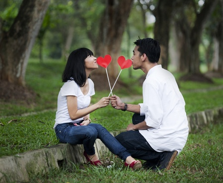 sit shape: Young couple with cutout of red heart in the nature