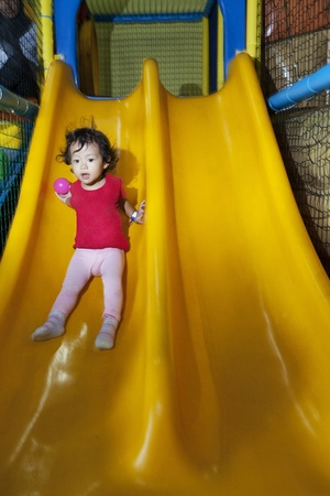 Cute little girl sliding on playground photo