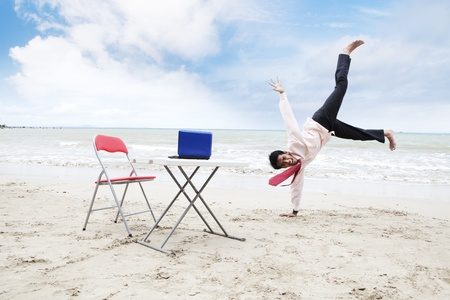 asian style: Attractive businessman dancing on the beach