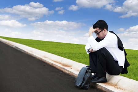 Depressed businessman sitting on the street with blue sky photo