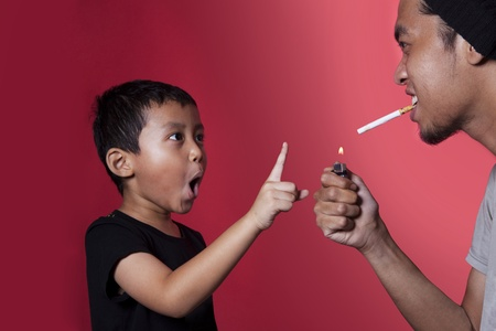 Asian kid asking a smoker to stop smoking shot over red background photo
