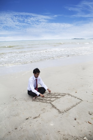 Businessman drawing a laptop on the sand photo