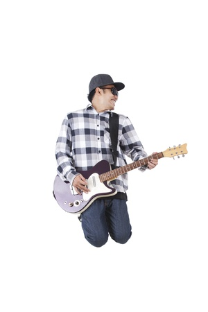 Asian man jumping while holding a guitar isolated on white photo